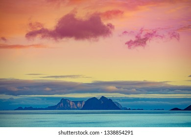 Island on the horizon. Rocks in the sea. Beautiful rocky sea landscape in evening. Wild nature Norway, Lofoten islands seascape. Gradient color