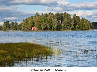 Island on lake in Finland with red summer cottage