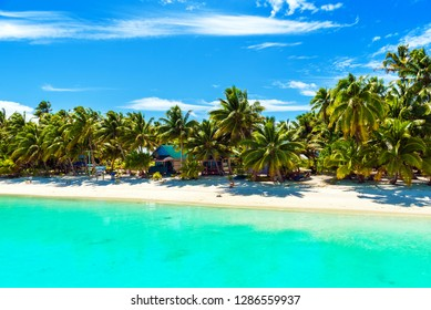 A island with palm trees, white sand, turquoise tranquil ocean water and blue sky at Cook Islands, South Pacific. Copy space for text