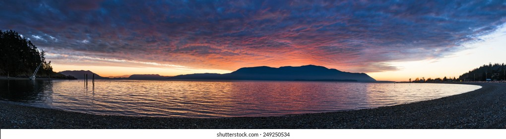 Island Panorama. Panoramic view of Orcas Island, in the Puget Sound area of western Washington, is enveloped in a fiery sunset seen along Legoe Bay on the shores of Lummi Island.