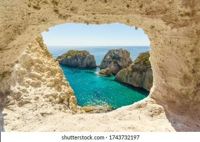 Island of Ponza, Italy. August 16th, 2017. An amazing view of three rocks in the sea, through an opening in the cliff. Framed naturally.