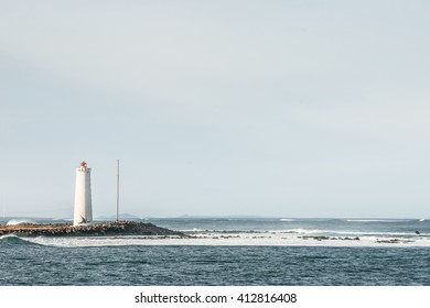 Island with a small lighthouse in a cold ocean