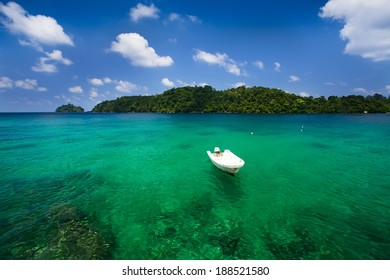 Islands in Indonesia in the turquoise sea with crystal clear water, boat, coral reefs and white sand for diving from a boat. Background blue sky with clouds.