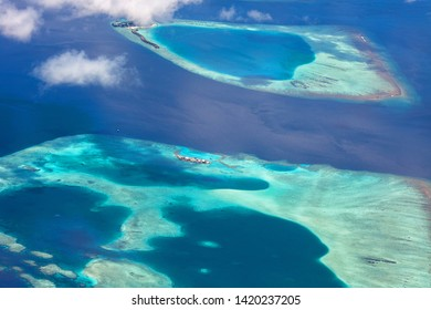 Islands Maldives view from the window of the plane. Beautiful atolls and bright colors of the sea.