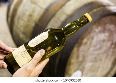 ISLAY, SCOTLAND - SEPT 13 2017: Someone holds a bottle of 16 years aged Lagavulin single malt whisky at the Lagavulin whisky distillery with old oak cask on the background.