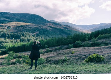 ISLE OF ARRAN, SCOTLAND - May 1, 2019: Young woman taking a picture of isle of Arran forest.