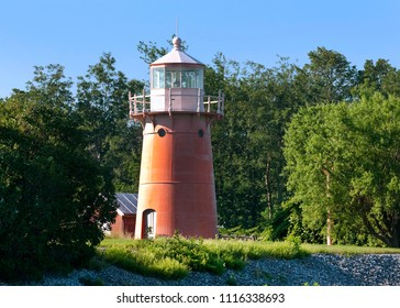 Isle La Motte lighthouse, with its rustic pink tower on a summer day in Vermont.