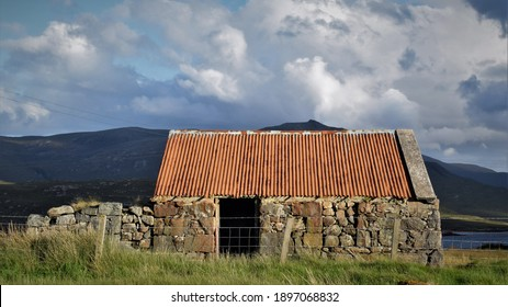 Isle of Lewis, Scotland - June 2 2017: A tumbledown stone building with a tin roof at the road side in the Outer Hebrides