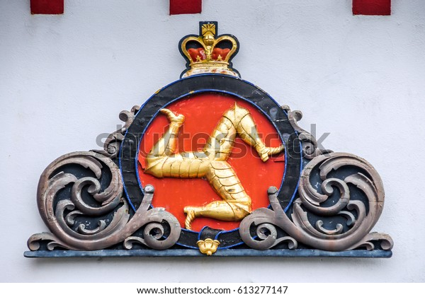 Isle of Man, Douglas, 7 June 2016: Isle of Man symbol. Isle of Man flag. Design of Isle of Man flag. Country symbol tree legs. Country flag Retro country symbol shape on the building.UK country crown