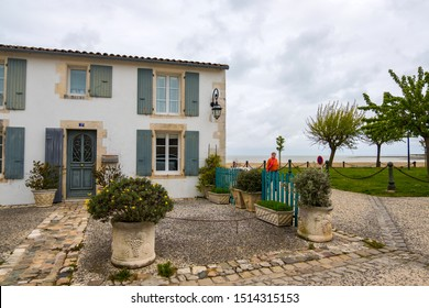 Isle of Re, France - May 09, 2019: House on Atlantic coast. La Flotte village on Ile de Re island in France. Woman walking on the road