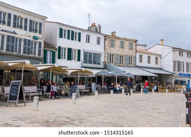 Isle of Re, France - May 09, 2019: People relax in traditional French street cafes on quayside of La Flotte village on Ile de Re island in France