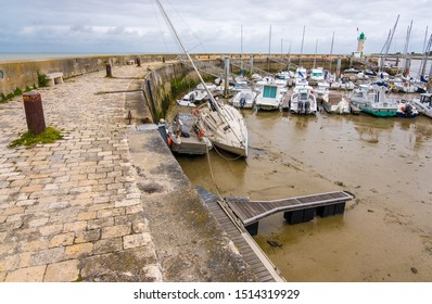 Isle of Re, France - May 09, 2019: lighthouse and boats in harbor of La Flotte on Ile de Re island. It is one of the most beautiful villages in France