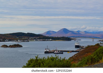 Isle of skye looking towards the bridge into skye with the mountain highlands in the background and fishing boats in the foreground and a little village of houses to the left