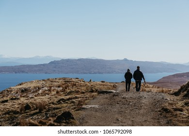 ISLE OF SKYE, SCOTLAND - MARCH 19, 2018: Couple walking the Old Man of Storr walk on Skye, mountains and lake on the background. The Storr trek is the most famous and busiest walk on the Island.
