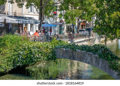 ISLE SUR LA SORGUE, FRANCE - AUGUST 31, 2020. In a district of the city center, A small stone bridge over the Sorgue, Filled with greenery.