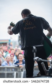 Isle of Tiree, Argyll / UK - 07 13 2019: looking from behind a guitarist on a stage at the crowd enjoying a festival performance