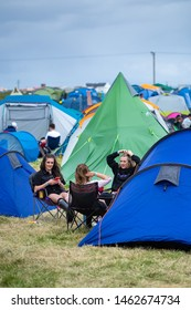 Isle of Tiree, Argyll / UK - 07 13 2019: three beautiful women sitting in camping chairs on a festival campsite relaxing, chatting and having fun