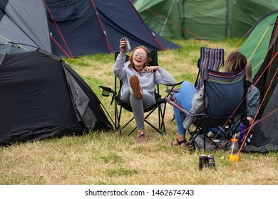 Isle of Tiree, Argyll / UK - 07 13 2019: two women wearing glasses sitting in camping chairs on a festival campsite relaxing, drinking, chatting and having fun
