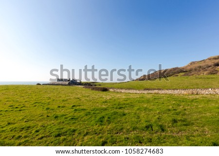 Isle of Wight, England, green land at Watershoot Bay. Landscape with bright green grass and blue sky, English Channel in bacground and small old house in middle. Low horizon