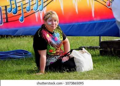 Isle of Wight Festival - June 11th 2016 Solo woman with glitter and face paint sitting with a canvas bag enjoying the festival, Newport Isle of Wight, June 11th 2016, Isle of Wight, UK