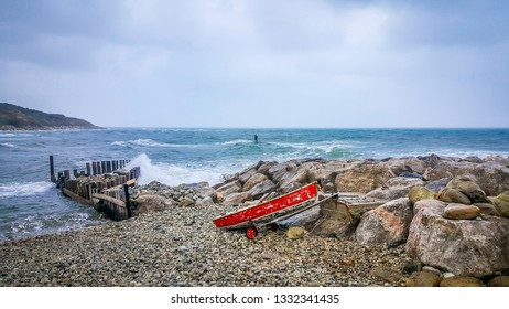 Isle of Wight, United Kingdom - August 28, 2018:  stormy weather, an old boat on a beach