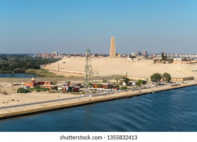 Ismailia, Egypt - November 5, 2017: Military built and telecommunication tower on the shore of the Suez Canal near Ismailia, Egypt, Africa. Suez Canal Defence Monument in the background.