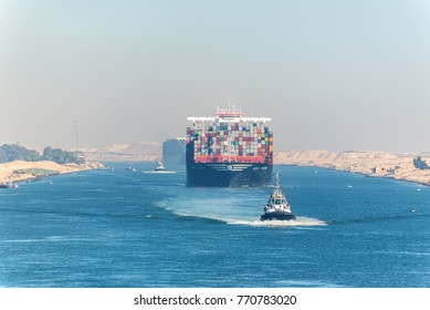 Ismailia, Egypt - November 5, 2017: Large container vessel ship MSC Maya passing Suez Canal in the sandy haze in Egypt. Tugboat accompanies the ships.
