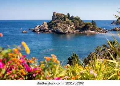 The Isola Bella island and beach with blurred flowers in the front in Taormina, Italy