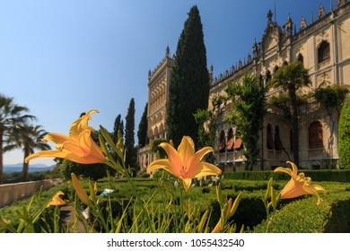 Isola del Garda, Italy - May 28, 2017: Lillies in front of venetian neogothic building of Villa Borghese Cavazza with garden