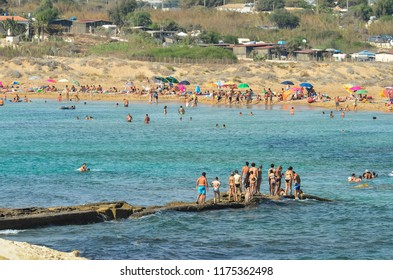 Isola delle Correnti, Sicily (Syracuse), Italy - August 2012: Isola delle Correnti and Capo Passero summer sandy sea beach, the most southern point in Sicily. People crossing the sea to the Island.