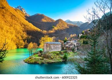 Isola Santa medieval village, church, lake and Alpi Apuane mountains. Garfagnana, Tuscany, Italy Europe