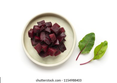 Isolared beetroot on white surface with green beet leaves. Top view.