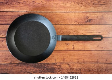 Isolate carbon steel skillet pan on a wooden background - overhead top view of flat lay concept. Professional grade cookware utensil equipment used in restaurants - industry standard for stove top.