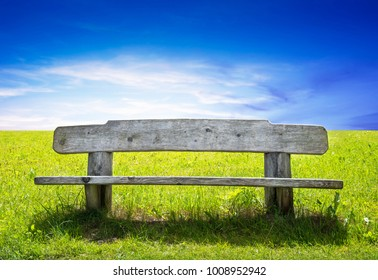 isolate wooden bench in green field