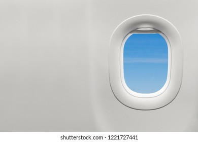Isolated airplane window with blue sky from customer seat view