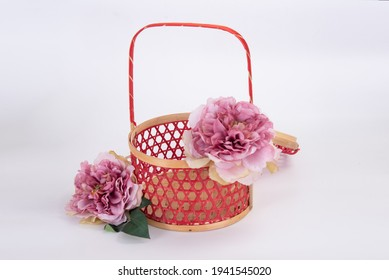 Isolated angled view of red Chinese style rattan basket with pink flower decoration on white background