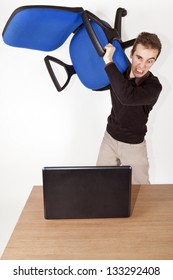 isolated angry business man with office chair in his hand above his head ready to destroy a laptop