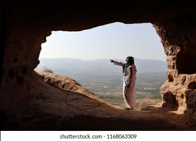 ISOLATED ARABIC MAN POINTING OUT FROM A CAVE