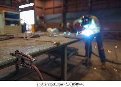 Isolated arc welder using earth clamp on the side table with defocused welder performing welding steel bolts into the metal plate at the construction fabrication site work shop