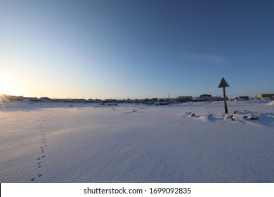 Isolated arctic landscape with Inuit community in the background and single set of footsteps in the snow, Rankin Inlet, Nunavut Canada