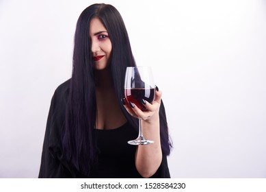 isolated Asian long haired woman with spooky makeup in black dress smiling and holding a glass of red wine on white background