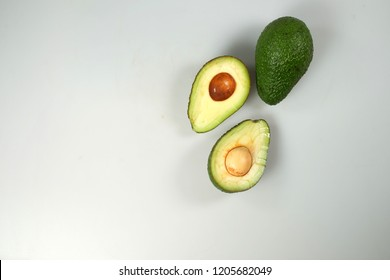 Isolated avocado. Whole avocado fruit and two halves in a row isolated on white background with clipping path. Top view