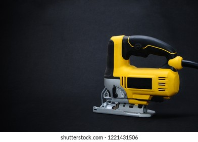 Isolated back side yellow electric jig saw on a dark background