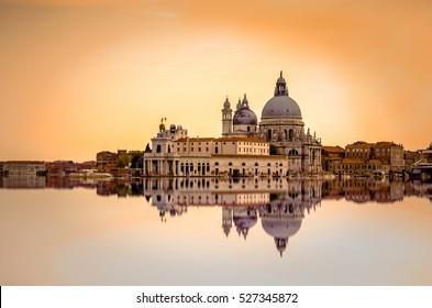 Isolated Basilica di Santa Maria della Salute at orange colors reflected on the water surface, Venice, Italy.