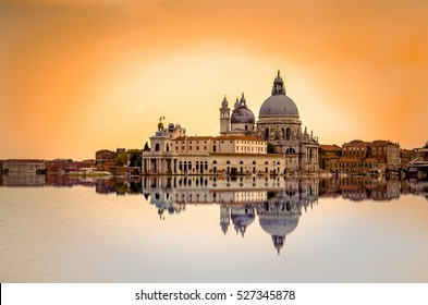 Isolated Basilica di Santa Maria della Salute at orange colors reflected on the water surface, Venice, Italy.