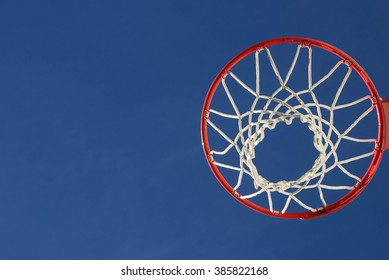 Isolated basketball net shot directly below and looking up with the blue sky as the background.