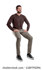 An isolated bearded man in casual wear sits on a white background with hands on his thighs. Sitting and waiting. Meditating. Neutral expression.
