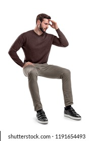An isolated bearded man in casual wear sits on a white background with one hand touching his forehead. Thinking about troubles. Unresolved problems. Headache.