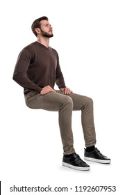An isolated bearded man in casual wear sits on a white background with hands on his thighs and looks up. Searching for answers. Waiting for help. Thinking of problems. - Shutterstock ID 1192607953