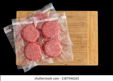 Isolated beef burger patties prepared for freezing vacuum packed in clear plastic ready for sous-vide cooking in a top down view on a wooden board on black